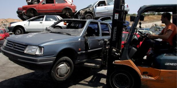 A worker transports a junked car