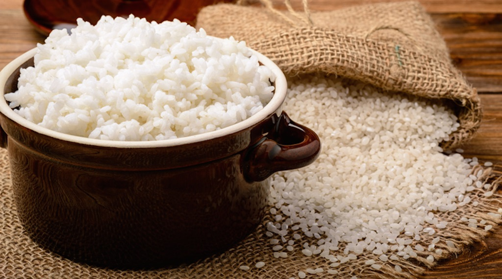 Boiled white rice in ceramic pot on wooden background.